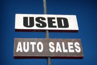 aged and worn vintage photo of used cars sign